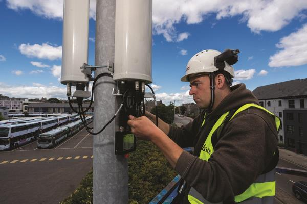 An engineer installs a small cell radio for O2 on a lamppost in Aberdeen.