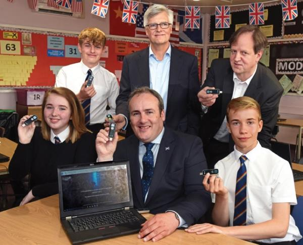Pupils at the academy show off their LiFi-XC Stations that plug into their laptops. Also pictured: pureLiFi CEO Alistair Banham (standing centre); Professor Harald Haas (standing right); and Scottish MSP Paul Wheelhouse (seated middle).